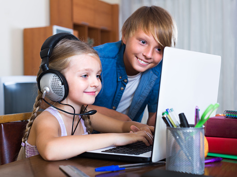 Portrait of happy children burying in notebook and busy with game